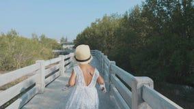 Gelukkige leuk weinig kindmeisje stelt op mangroven bosweg in werking stock videobeelden