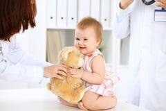 Gelukkige leuke baby na gezondheidsexamen op artsen` s kantoor Royalty-vrije Stock Afbeelding