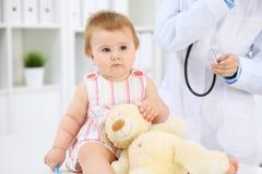 Gelukkige leuke baby na gezondheidsexamen op artsen` s kantoor Stock Afbeelding