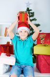 Gelukkige leuke die kindjongen in Kerstmanhoed door de kleurrijke dozen van de Kerstmisgift wordt omringd Stock Afbeeldingen