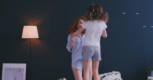 Gelukkige leuke dochter en jonge moeder die en op bed springen dansen terwijl pret thuis tijdens vakantie hebben stock footage