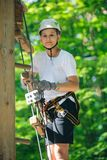Gelukkige, leuke, jonge jongen in witte t-shirt en helm die pret hebben en bij avonturenpark spelen, stock afbeelding