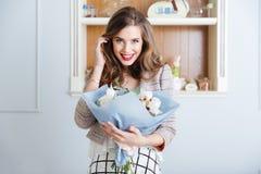 Gelukkige leuke jonge vrouw met boeket van bloemen in koffie royalty-vrije stock afbeeldingen