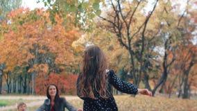 Gelukkige leuke meisjelooppas aan haar moeder en broer door verbazende de herfststeeg in park langzame mo stock videobeelden