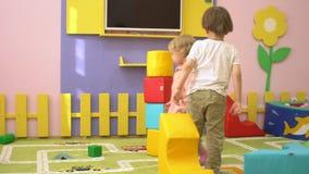Gelukkige leuke peuterkinderen die met multi gekleurde zachte blokken bij binnenspeelplaats spelen De activiteit van de kindsport stock video