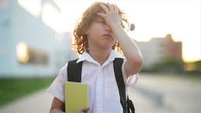 Gelukkige leuke slimme jongen met schooltas en boek in zijn hand Moderne rugzak Het kind is bereid te antwoorden Eerste keer aan stock video