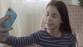 Gelukkige leuke tiener die een selfie dicht opnemen door haar blauwe cellphonezitting in de leunstoel thuis Een onbezorgd kind stock video