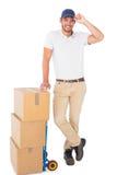 Gelukkige leveringsmens die op karretje van dozen leunen Stock Foto's