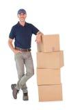 Gelukkige leveringsmens die op stapel van kartondozen leunen Stock Foto's