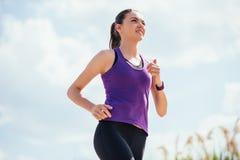 Gelukkige lopende glimlachende vrouw in purpere t-shirt en op blauwe hemelachtergrond Training Openlucht stock afbeelding