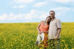 Gelukkige man en vrouw in gele weide stock afbeeldingen