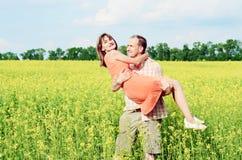 Gelukkige man en vrouw in gele weide royalty-vrije stock afbeelding
