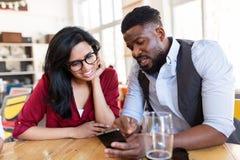 Gelukkige man en vrouw met smartphones bij bar Royalty-vrije Stock Afbeelding