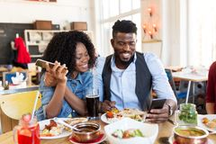 Gelukkige man en vrouw met smartphones bij restaurant stock foto
