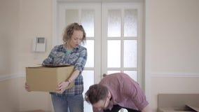 Gelukkige man en vrouw in toevallige kleding met dozen in handen die zich in de ruimte bevinden die rond dichte omhooggaand kijke stock videobeelden