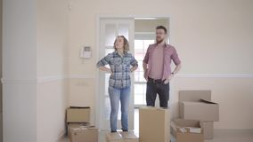 Gelukkige man en vrouw in toevallige kleding met dozen in handen die zich in ruimte bevinden Echtpaarbewegingen in een nieuw huis stock video