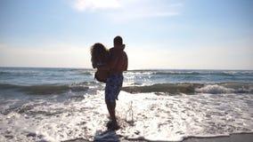 Gelukkige man holdingsvrouw in zijn wapens en het spinnen rond op overzees strand Jonge kerel die zijn meisje in zijn handen omci stock video