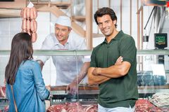 Gelukkige Man met Vrouw het Kopen Vlees bij Slachterij stock foto