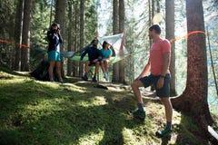 Gelukkige man vier en vrouwen hangende tent die in boshout tijdens zonnige dag dichtbij meer kamperen Groep de zomer van vrienden Royalty-vrije Stock Fotografie