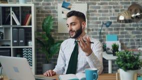 Gelukkige manager met laptop communiceren en oortelefoons die in notitieboekje schrijven stock video