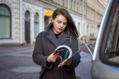 Gelukkige maniervrouw die een tijdschrift op een stadsstraat lezen stock foto's