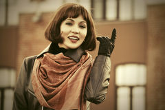 Gelukkige maniervrouw die in leerlaag op stadsstraat lopen Royalty-vrije Stock Foto's