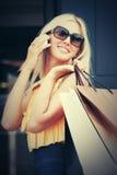 Gelukkige maniervrouw die met het winkelen zakken mobiele telefoon uitnodigen Royalty-vrije Stock Fotografie