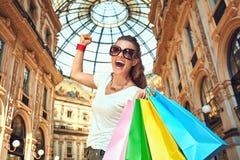 Gelukkige maniervrouw die met het winkelen zakken zich in Galleria verheugen stock fotografie