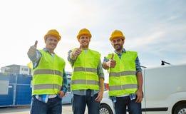 Gelukkige mannelijke bouwers in hoge zichtbare vesten in openlucht royalty-vrije stock afbeelding