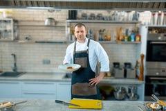 Gelukkige mannelijke chef-kok die de schotel in commerciële keuken voorstellen royalty-vrije stock afbeeldingen