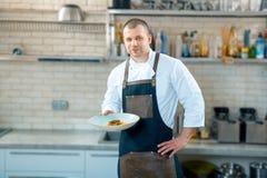Gelukkige mannelijke chef-kok die de schotel in commerciële keuken voorstellen royalty-vrije stock foto