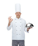 Gelukkige mannelijke chef-kokkok met glazen kap die o.k. teken tonen Stock Foto