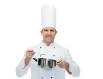 Gelukkige mannelijke chef-kokkok met pot en lepel Royalty-vrije Stock Foto's