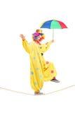 Gelukkige mannelijke clown die met paraplu op een kabel lopen Royalty-vrije Stock Fotografie