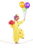 Gelukkige mannelijke clown die op een kabel met bos van ballons en PR lopen Stock Foto's