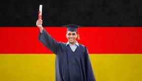 Gelukkige mannelijke student met diploma over Duitse vlag stock foto's