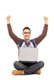 Gelukkige mannelijke studentenzitting met laptop en een gesturing geluk Stock Afbeeldingen