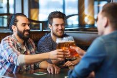 Gelukkige mannelijke vrienden die bier drinken bij bar of bar Royalty-vrije Stock Afbeeldingen