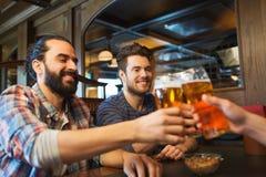 Gelukkige mannelijke vrienden die bier drinken bij bar of bar Stock Fotografie
