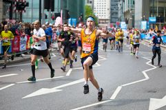 Gelukkige Marathonagent die door publiek toejuichen Het liefdadigheidsgeld heft op Londen, het UK royalty-vrije stock afbeelding