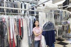Gelukkige medio volwassen vrouw die omhoog terwijl het zetten van kleren in plastiek kijken Stock Foto