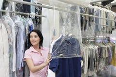 Gelukkige medio volwassen vrouw die weg terwijl het zetten van kleren in plastiek kijken Stock Foto's