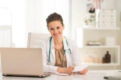 Gelukkige medische artsenvrouw die in bureau werken royalty-vrije stock afbeelding