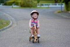 Gelukkige meisje berijdende driewieler op de straat Stock Foto's