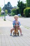 Gelukkige meisje berijdende driewieler op de straat Stock Foto