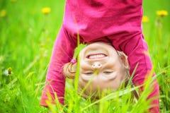 Gelukkige meisje bevindende bovenkant - neer op gras in de zomerpark Stock Afbeeldingen