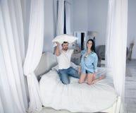 Gelukkige meisje en jongensspelhoofdkussens op het bed het is een echte liefde royalty-vrije stock afbeelding