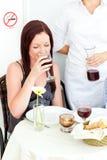 Gelukkige meisje het drinken wijn bij het restaurant Royalty-vrije Stock Afbeelding