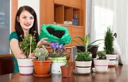Gelukkige meisje het overplanten ingemaakte bloemen stock fotografie