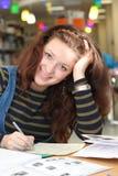 Gelukkige meisje het schrijven nota's in universiteitsbibliotheek royalty-vrije stock foto